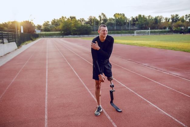 달리기 트랙에 서서 고통스러운 팔을 들고 인공 다리를 가진 스포티 한 백인 남자. 프리미엄 사진