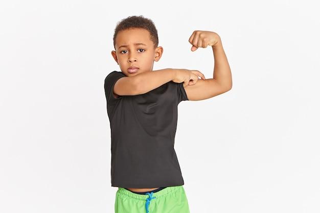 Спортивный, уверенный в себе африканский мальчик в спортивной одежде, напрягающий бицепс, демонстрируя силу и физическую выносливость. симпатичный атлетичный темнокожий ребенок гордится собой и демонстрирует свои напряженные мышцы рук Бесплатные Фотографии