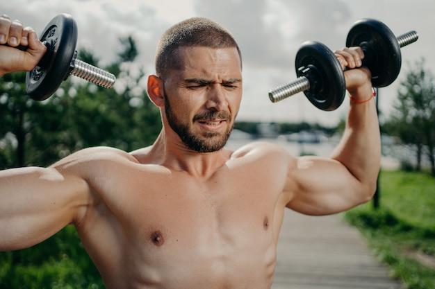 스포티 한 결정된 근육 유럽 남자 아령으로 Exercsises 프리미엄 사진