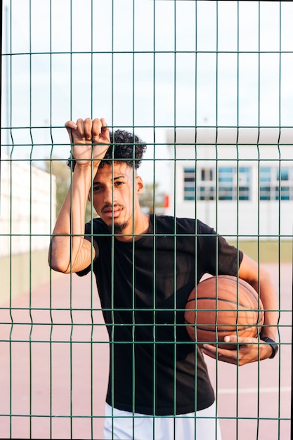 Sporty ethnic man holding basketball behind fence Free Photo