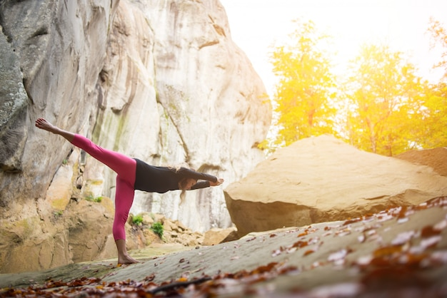 Sporty fit girl practicing yoga and outdoors. huge rocks on the background Premium Photo