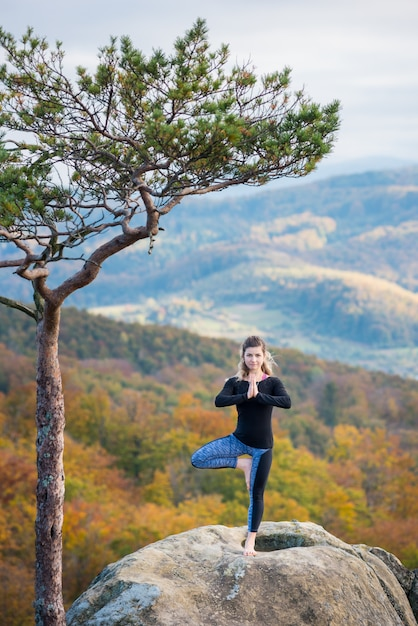 Sporty fit woman is practicing yoga on the top of the mountain Premium Photo