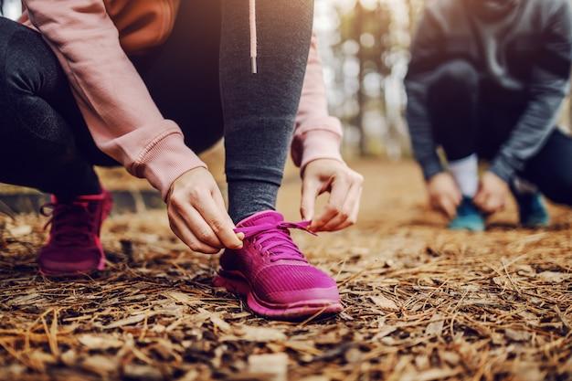 自然の中でトレイルにしゃがみ込んで走る準備をしながら靴紐を結ぶスポーティなフィットの若い女性。 Premium写真