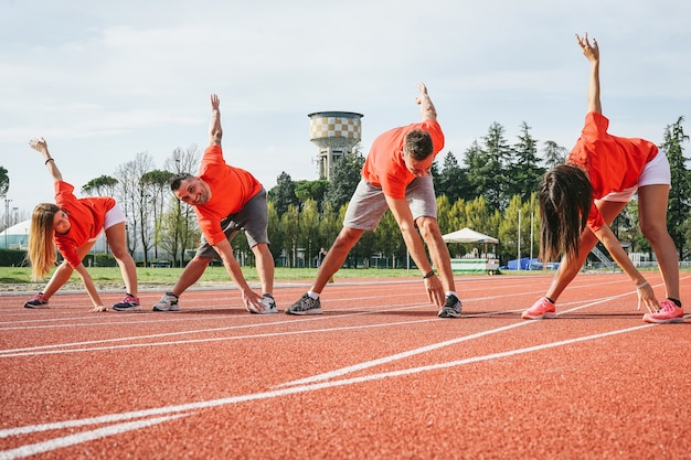 Sporty friends streching legs before running young runners training together outdoor Premium Photo