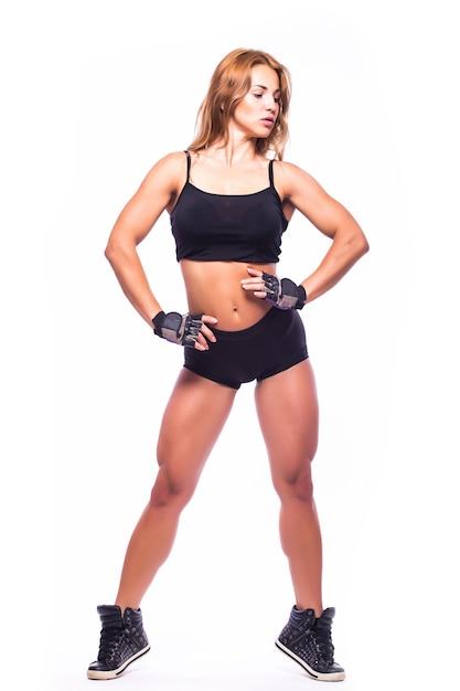 Ragazza sportiva facendo esercizi di boxe, facendo un colpo diretto. ragazza giovane isolata sulla parete bianca. forza e motivazione. Foto Gratuite