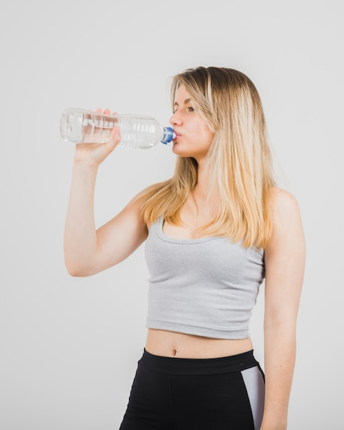 Sporty girl drinking water Free Photo
