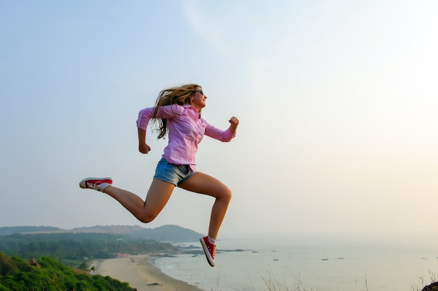 Sporty girl in shirt, shorts and sneakers depicts running in the air on a hill against the sea Premium Photo