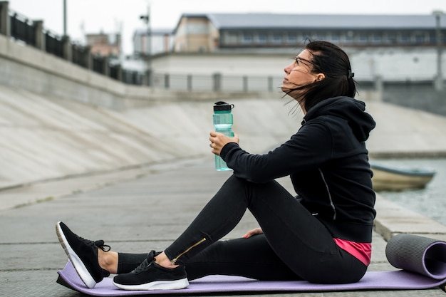 Sporty girl sitting with bottle of water Free Photo