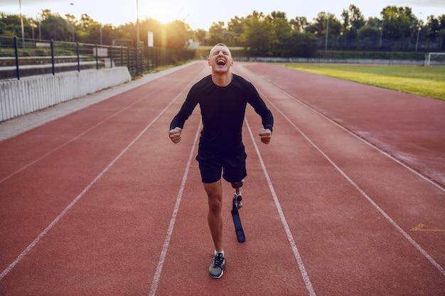 경마장에 서서 달리기 위해 자신을 동기 부여하는 인공 다리를 가진 스포티 한 잘 생긴 백인 장애인 남자. 프리미엄 사진