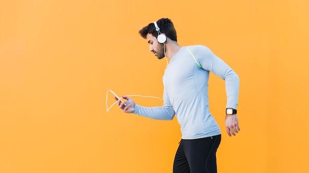 Sporty man choosing music on smartphone Free Photo