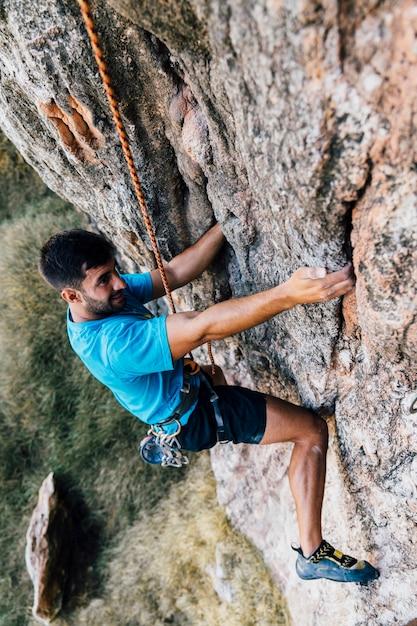 Sporty man climbing on rock Premium Photo
