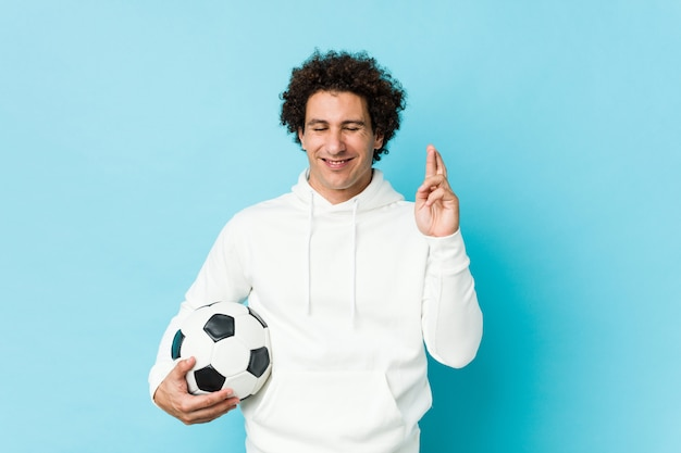 행운을 위해 축구 공을 건너 손가락을 잡고 스포티 한 남자 프리미엄 사진