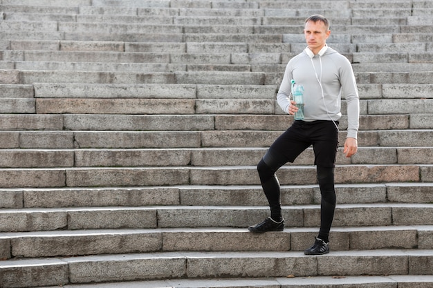 Sporty man holding a bottle of water on stairs Free Photo