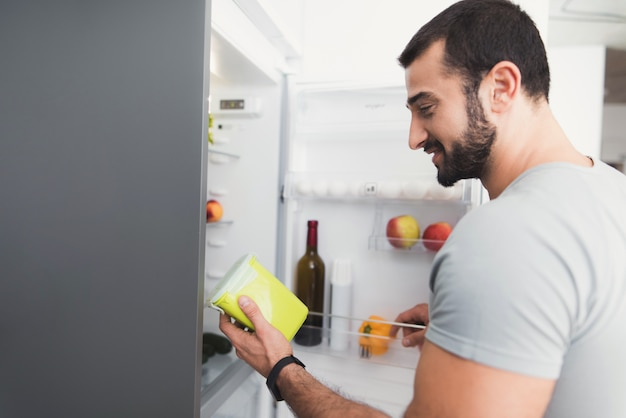 Sporty man stands in the kitchen and takes fresh vegetables Premium Photo