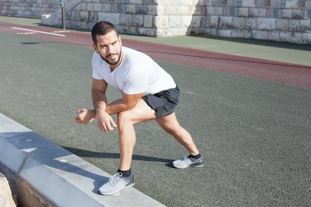 Sporty man stretching calf and leaning on knee Free Photo