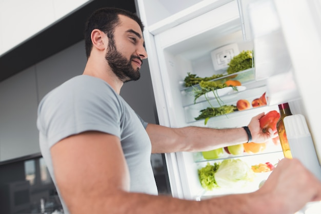 A sporty man takes vegetables from the fridge. Premium Photo