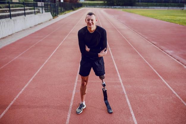 달리기 트랙에 서 있고 뱃속에 통증이있는 인공 다리를 가진 스포티 한 남자. 프리미엄 사진