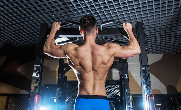 Sporty man with big muscles and a broad back trains in the gym, fitness and pumped-up abdominal press Premium Photo