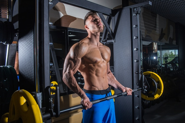 Sporty man with big muscles and a broad back trains in the gym, fitness Premium Photo