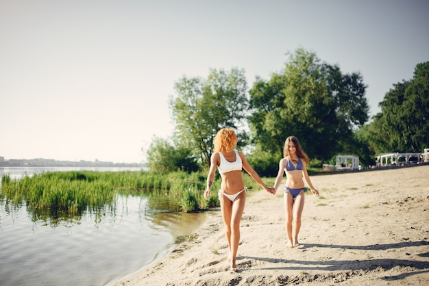 Sporty mother with cute daughter walking near lake Free Photo