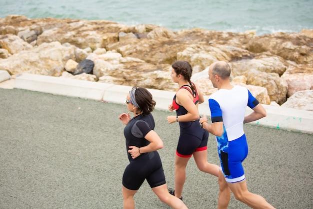 Sporty people running on sea coast Free Photo