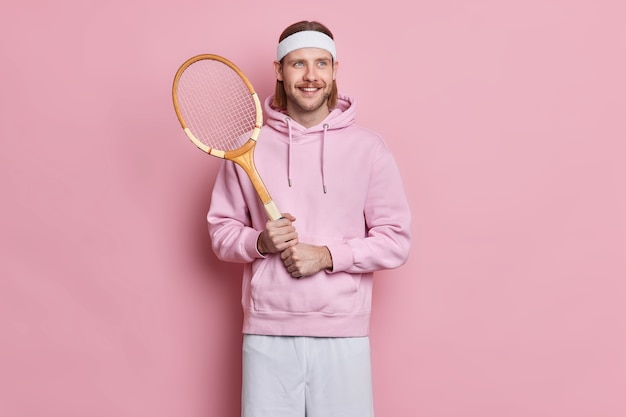 Sporty satisfied active man with mustache holds tennis raquet enjoys playing favorite game during spare time Free Photo