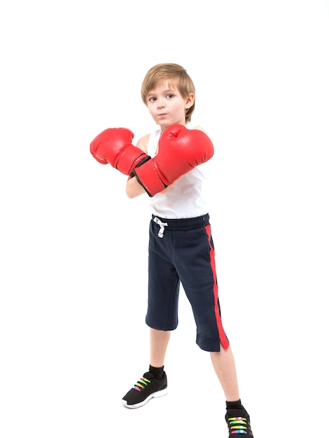 Sporty strong child boxing in red gloves Premium Photo