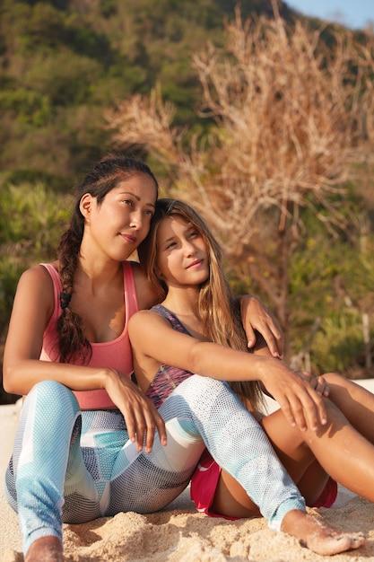 Due femmine sportive hanno espressioni pensose in lontananza, posano sulla natura Foto Gratuite