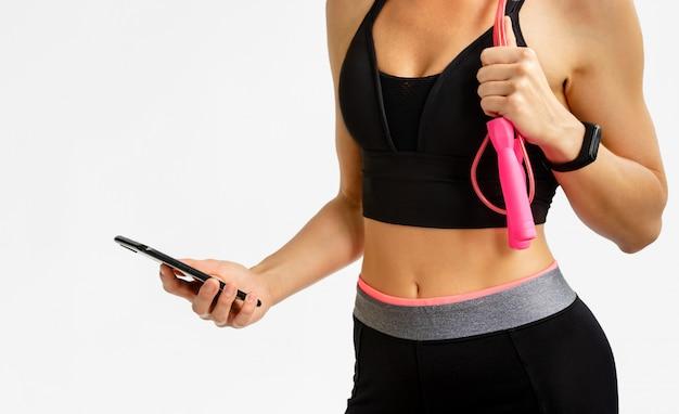 スポーティな女性がホワイトスペースにスマートフォンでフィットネストラッカーをチェックします。有酸素運動のコンセプトです。 Premium写真