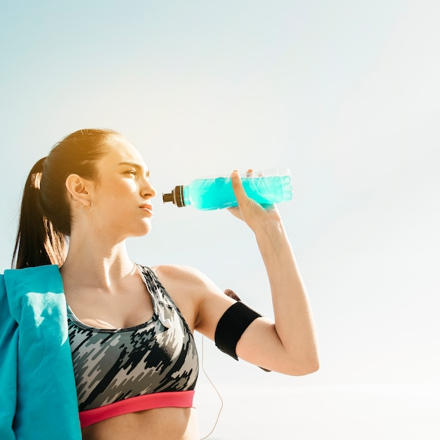 Sporty woman drinking on sky background Free Photo