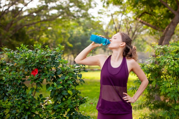 Sporty woman drinking water in park Free Photo