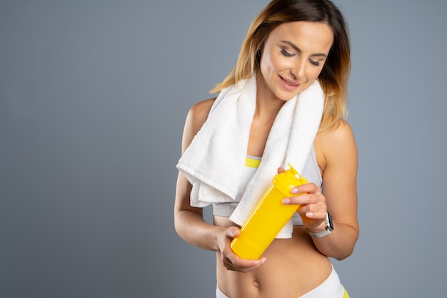 Sporty woman over gray background holding a bottle of water Premium Photo