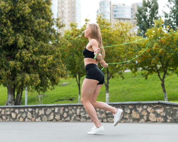 Спортивная женщина прыгает через скакалку Бесплатные Фотографии