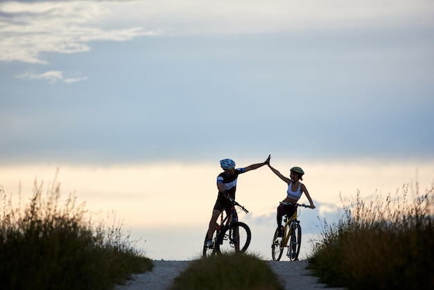 Sporty woman and man riding bicycles, having fun outside. silhouettes of sportsmen highing five and posing on road in sunset time. non urban scene. Premium Photo