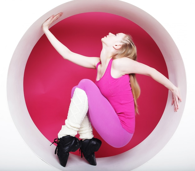 Sporty woman posing in pink circle Premium Photo