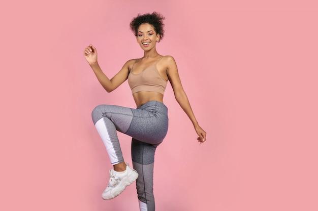 スポーティな女性がスタジオでスクワットの練習を練習します。ピンクの背景でワークアウトのスポーツウェアでアフリカの女性。 無料写真
