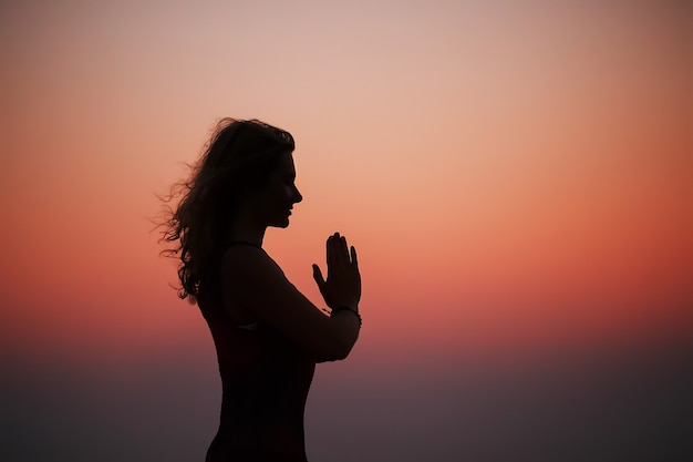 Sporty woman practicing yoga in the park at sunset Premium Photo