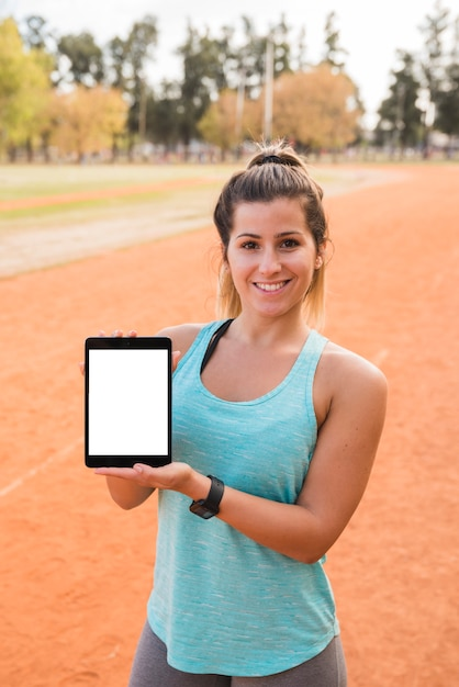Sporty woman presenting tablet template Free Photo