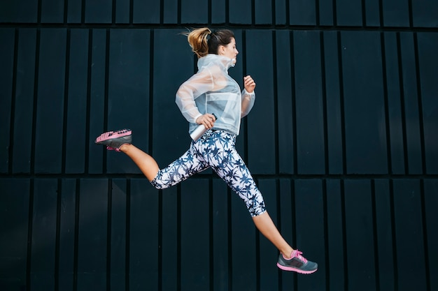 Sporty woman running in urban environment Free Photo