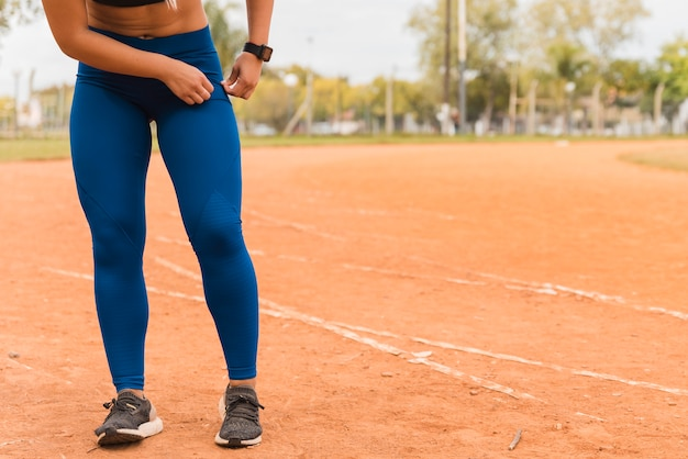 Sporty woman standing on stadium track Free Photo