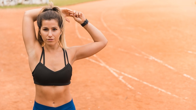 Sporty woman stretching on stadium track Free Photo