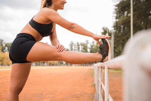 Sporty woman stretching on stadium track Free Photo