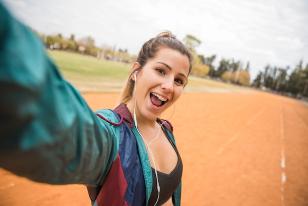 Sporty woman taking selfie on stadium track Free Photo
