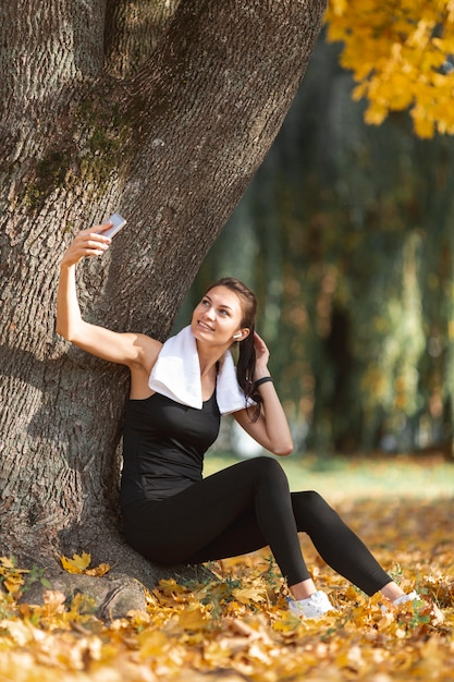 Sporty woman taking selfies close to a tree Free Photo