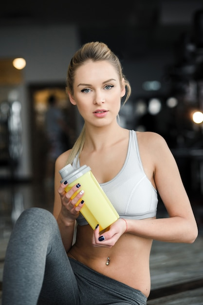 Sporty woman with bottle at the gym Free Photo