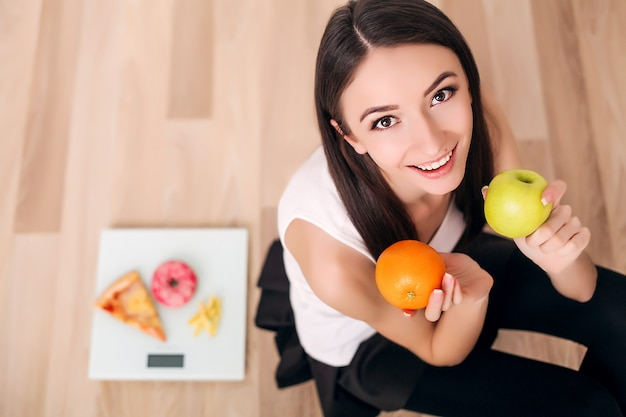 Sporty woman with scale and green apple and orange Premium Photo
