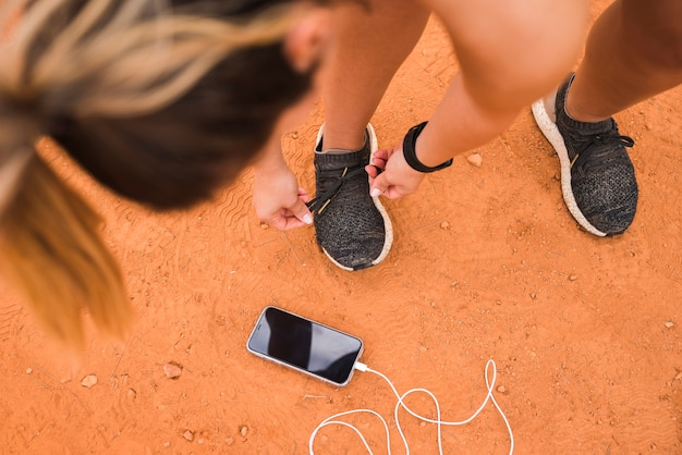 Sporty woman with smartphone on stadium track Free Photo