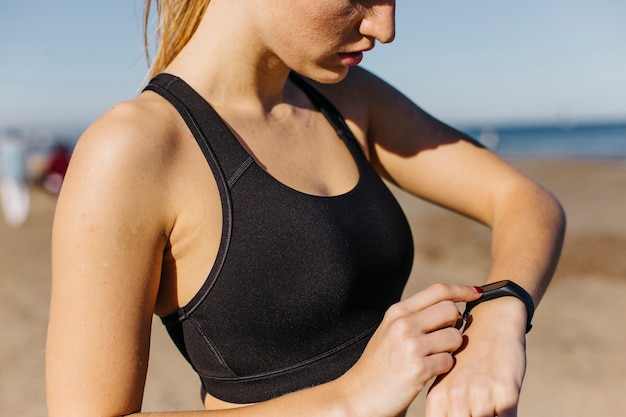 Sporty woman with smartwatch at the beach Free Photo