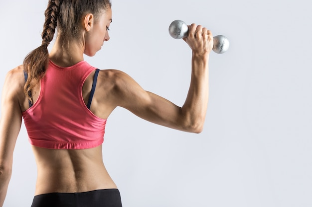 Sporty woman working out with weights. rear view Free Photo