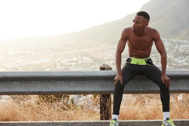 スポーティな青年はスピードを出して走り、山の近くの野外でトレーニングを終えて休憩し、スポーツトーナメントの準備をし、定期的な体操、屋外での余暇を過ごします。健康的な生活様式 無料写真
